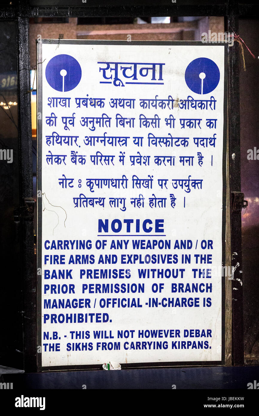 Notice about carrying firearms and explosives in the foyer of a bank where sihks are allowed to carry kirpans, Shillong, - Stock Image