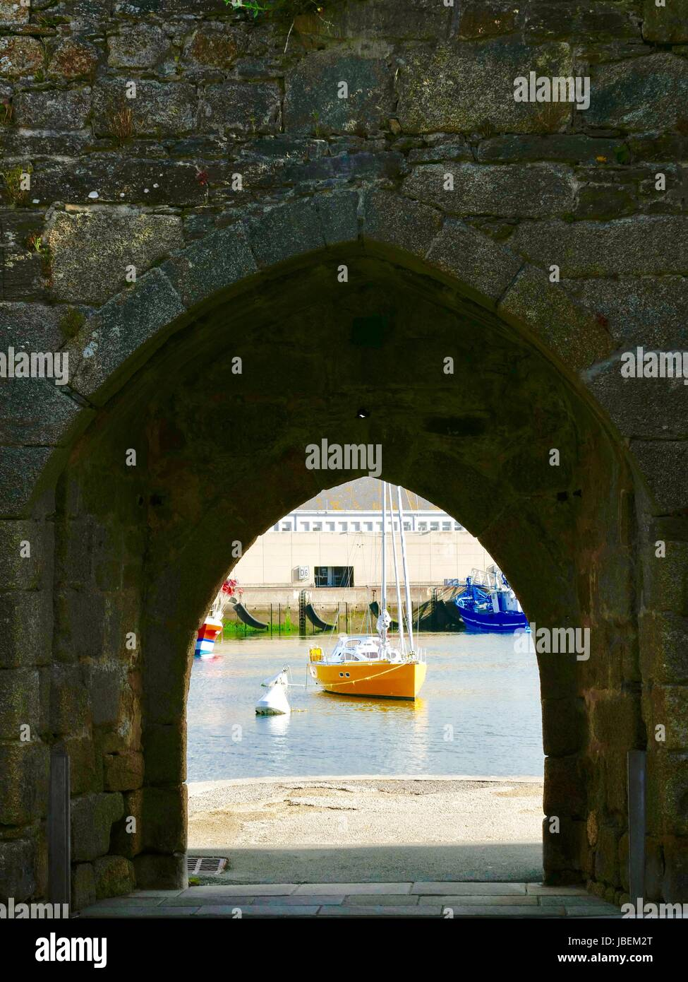 Sailboat with bright, yellow hull as seen through an arch in the medieval wall known as the wine gate, La Porte - Stock Image