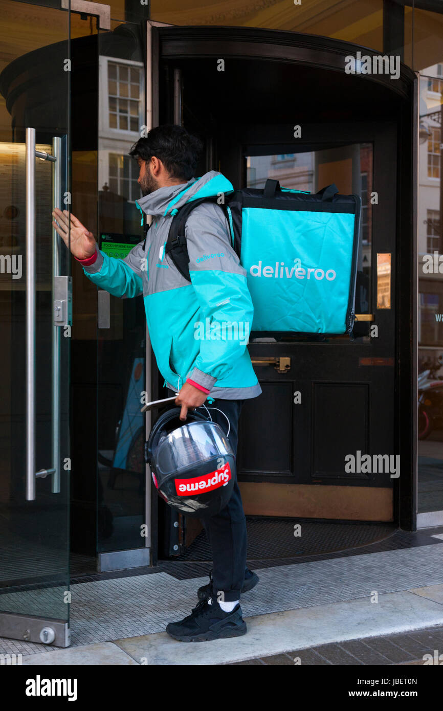 fd8b1693e12 Deliveroo takeaway food delivery Courier motor cyclist collecting a delivery  from a restaurant in Royal Leamington Spa. U.K. (88)