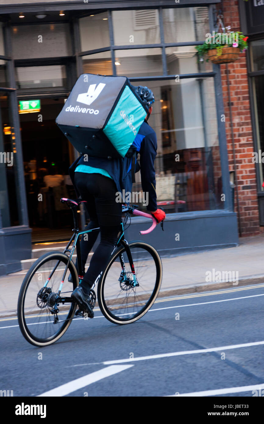 f2af4e0697b Deliveroo takeaway food delivery Courier pedal cycle / push bike cyclist  making a delivery run in