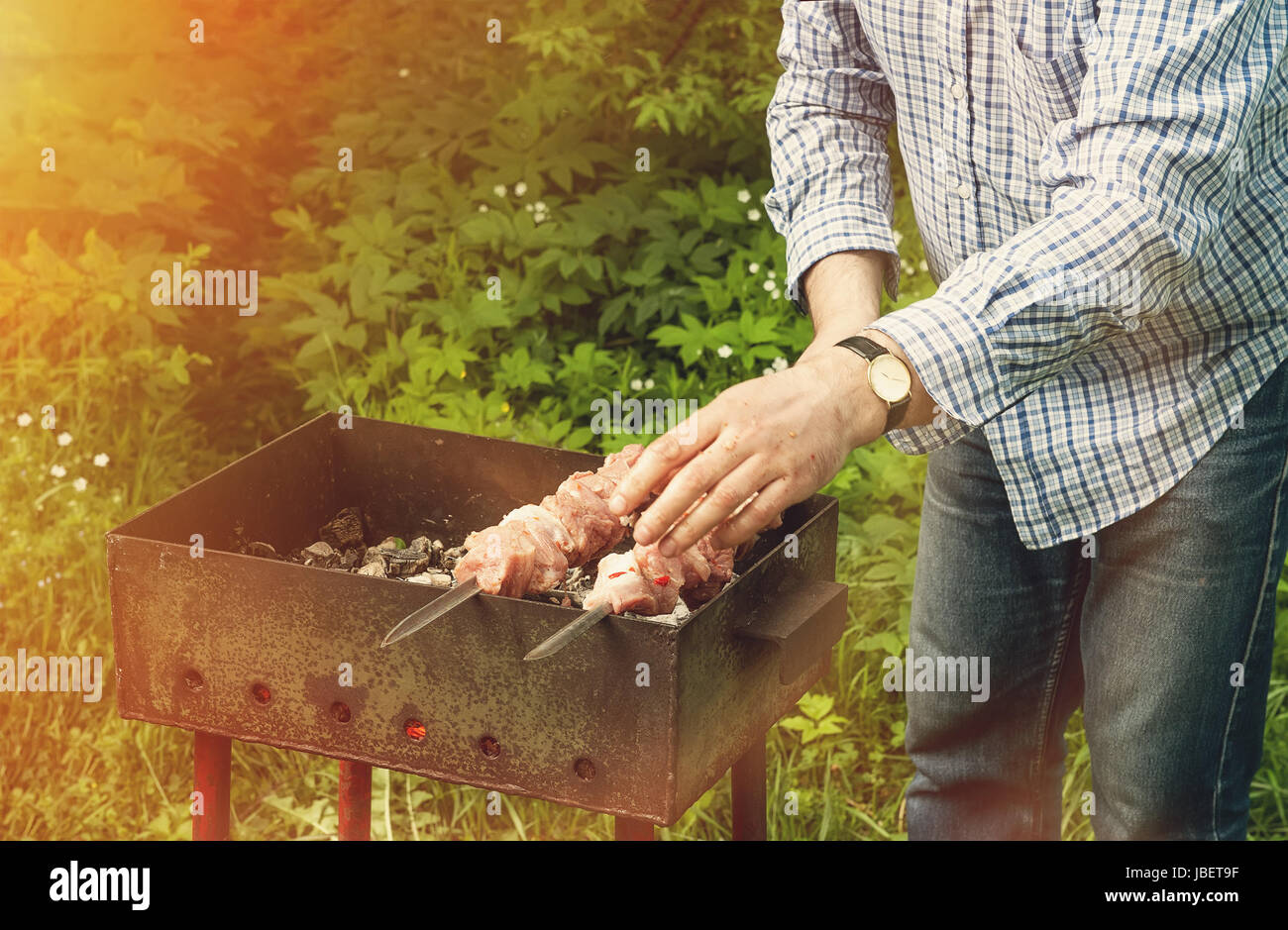 Delicious, juicy barbecue, roasted on a spit over an open fire. The hand holding the skewers.A horizontal frame. - Stock Image