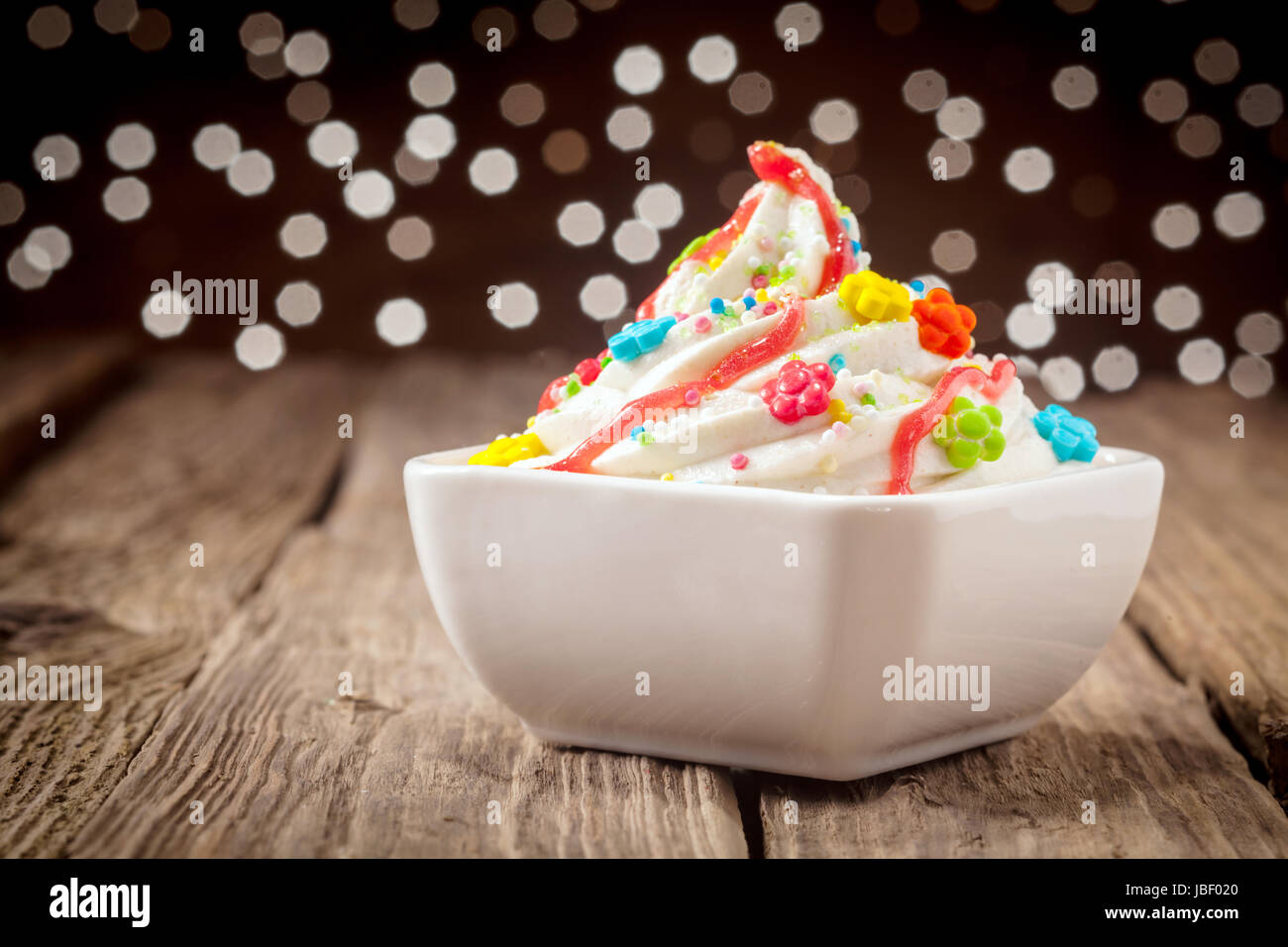 Colorful kids ice cream party dessert with a twirl of rich creamy vanilla ice cream topped with vibrant candy and Stock Photo