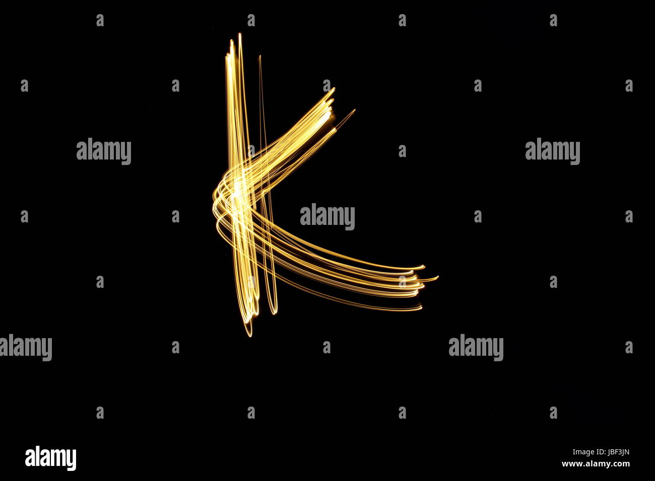 Gold letter K, Light Painting Photography, alphabet series, against a black background - Stock Image