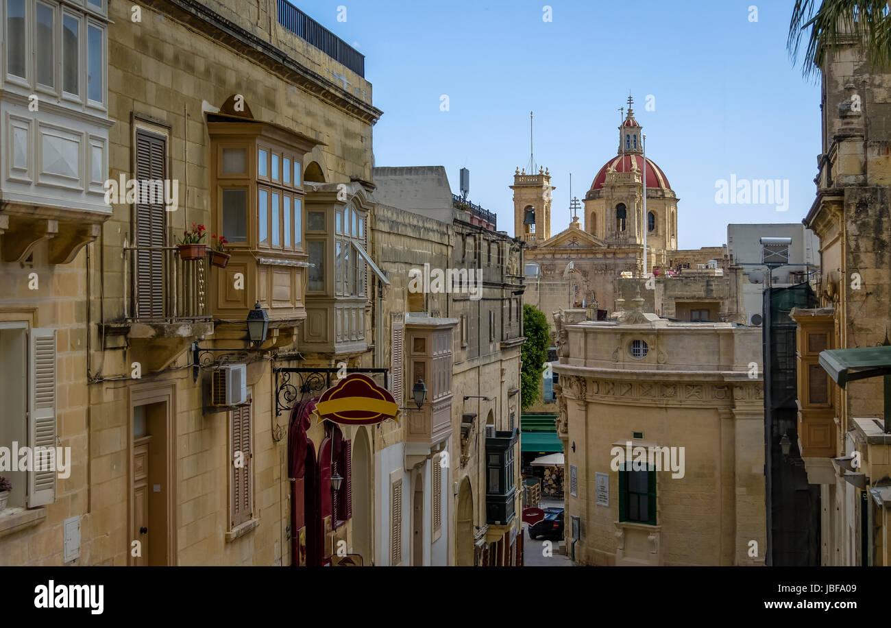 Victoria city street with Saint George Basilica red dome - Victoria, Gozo, Malta - Stock Image
