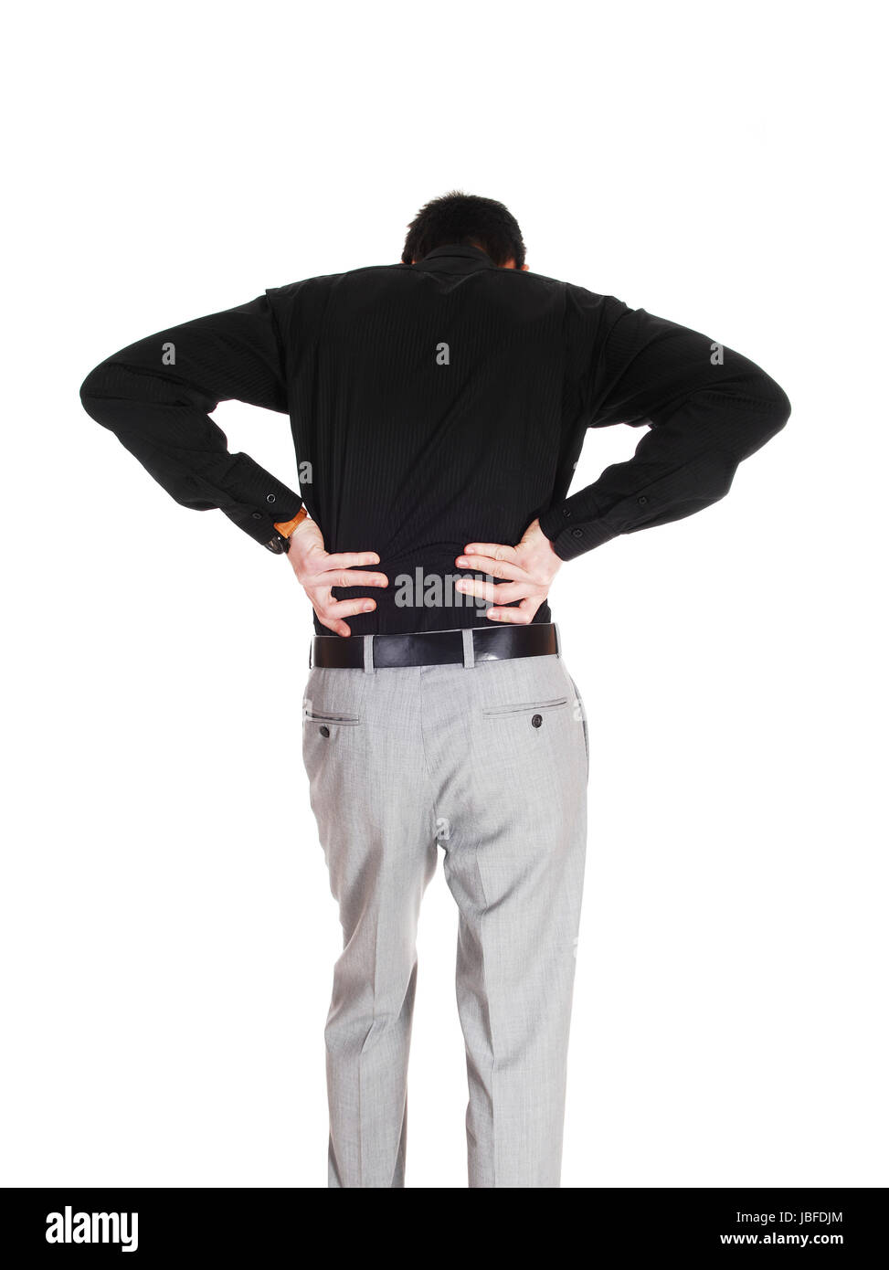 A young businessman standing from the back holding his hands on his back for heavy back pain, isolated for white - Stock Image