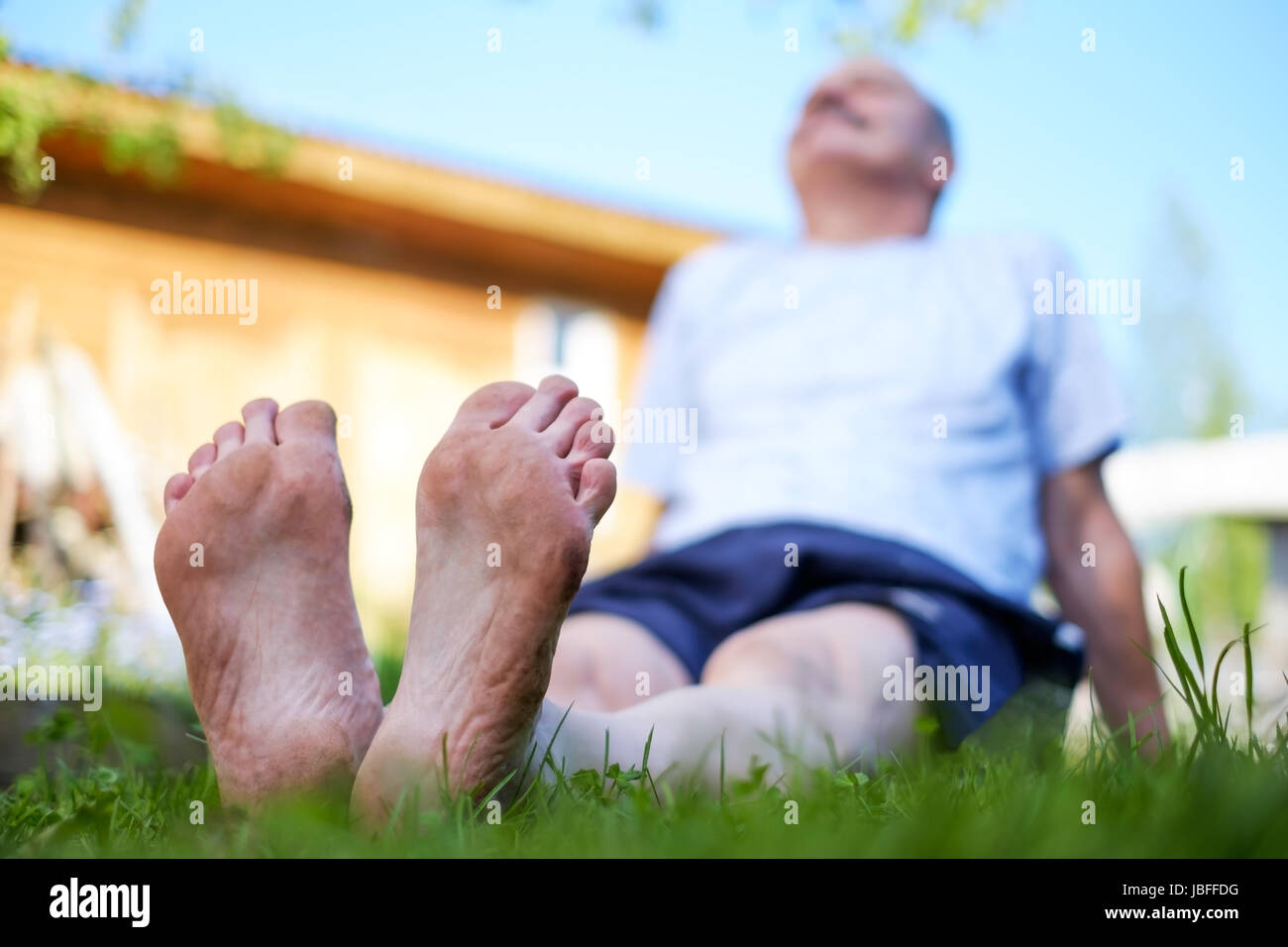 Man laying on grass field. He relax on nature in summer. Look up on sky - Stock Image