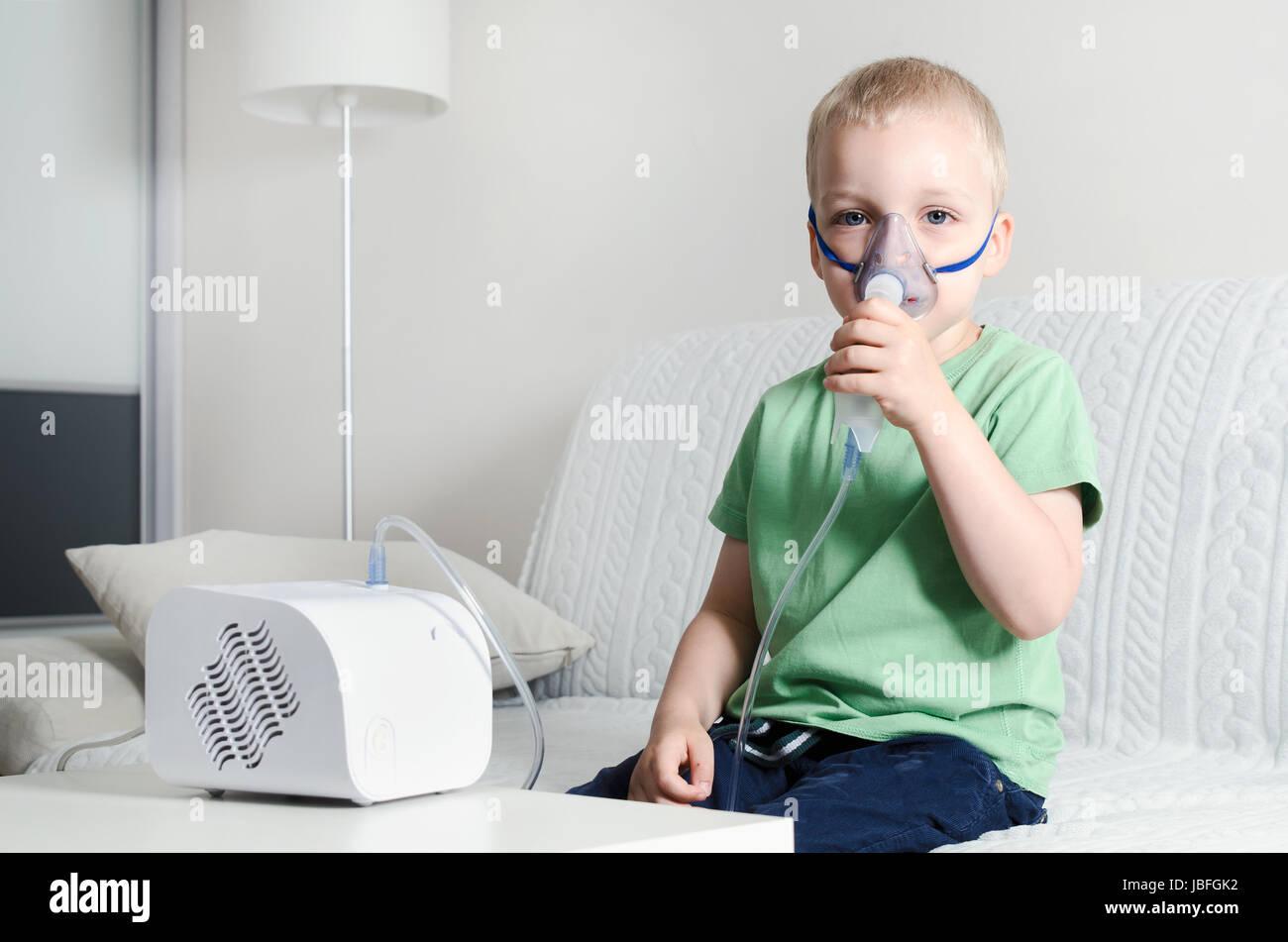 Boy making inhalation with nebulizer at home  child asthma inhaler