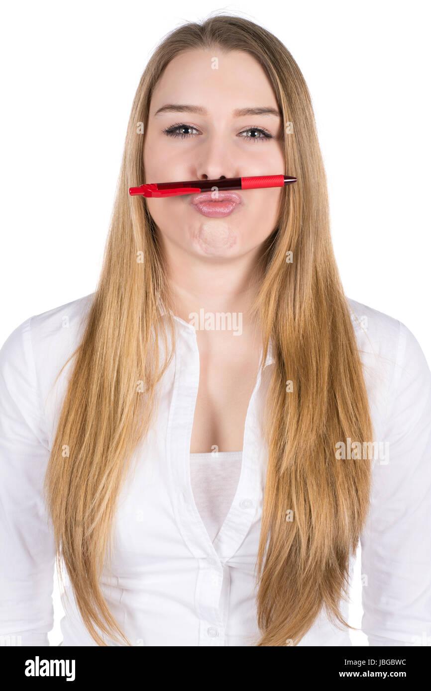 Freigestelltes Foto einer jungen Frau, die einen roten Kugelschreiber zwischen Nase und Mund hält Stock Photo