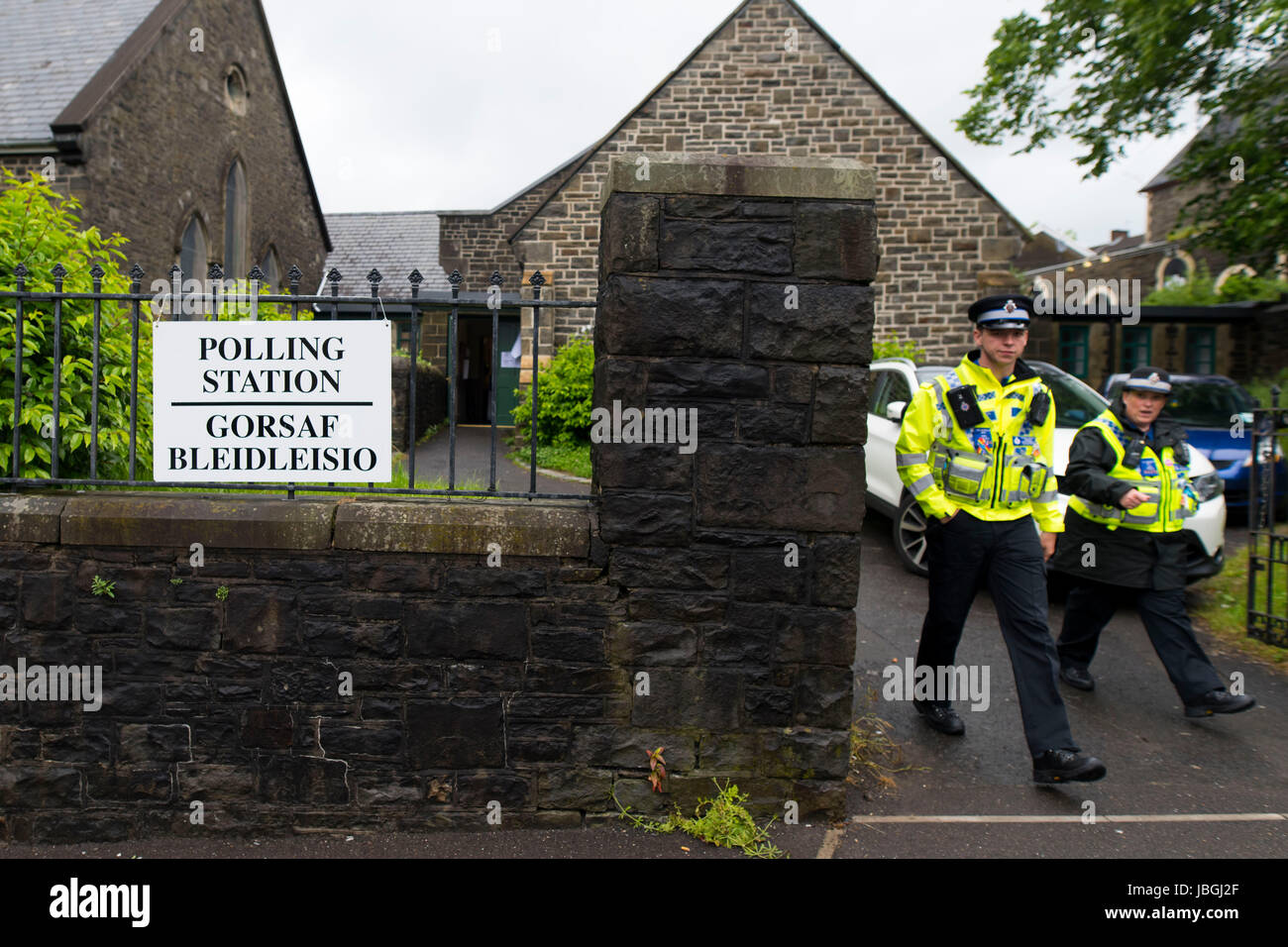 Two police officers leave a polling station in Merthyr, Wales, UK, on the day of the 2017 general election. - Stock Image