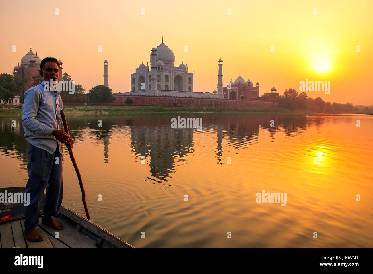 Local man steering boat on Yamuna river at sunset in front of Taj Mahal, Agra, India. It was build in 1632 by Emperor - Stock Image