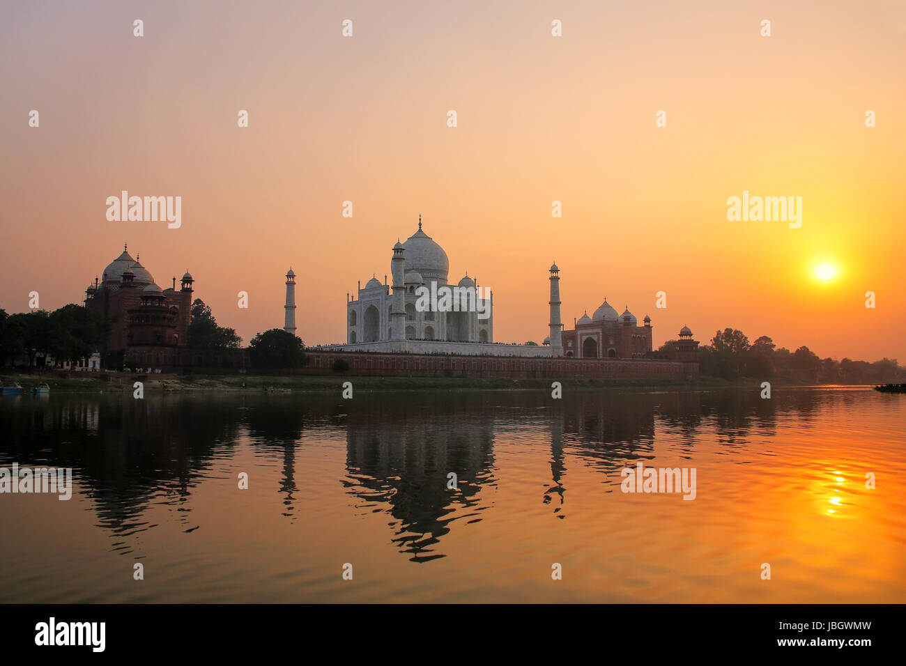 Taj Mahal reflected in Yamuna river at sunset in Agra, India. It was commissioned in 1632 by the Mughal emperor Stock Photo