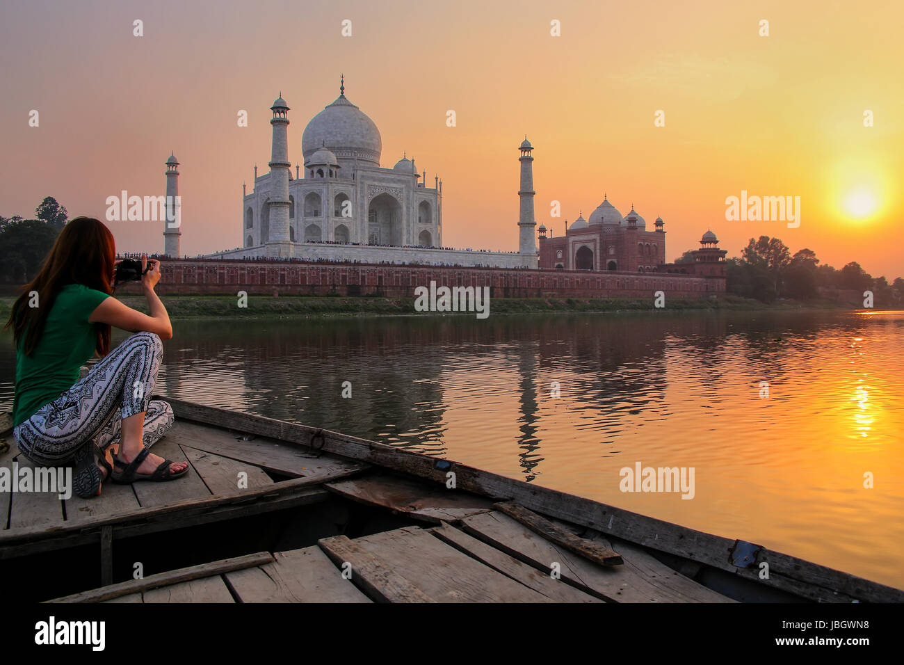 Woman watching sunset over Taj Mahal from a boat, Agra, India. It was build in 1632 by Emperor Shah Jahan as a memorial - Stock Image