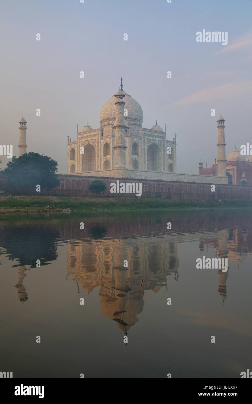 View of Taj Mahal with early morning fog reflected in Yamuna River, Agra, Uttar Pradesh, India. Taj Mahal was designated - Stock Image