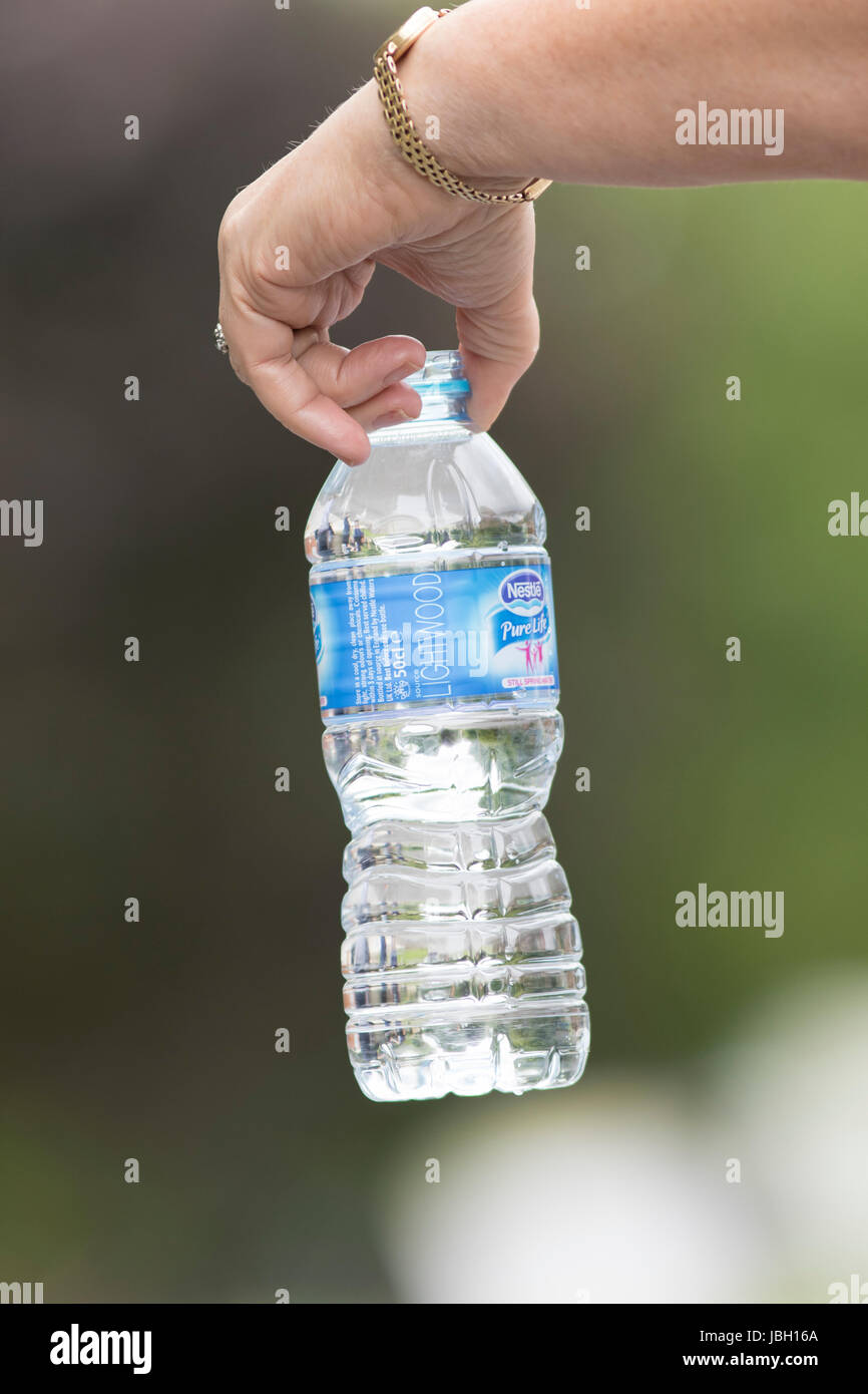 QUENINGTON, UK - JUNE 4, 2017: Hand holding a bottle of Nestle water - Stock Image