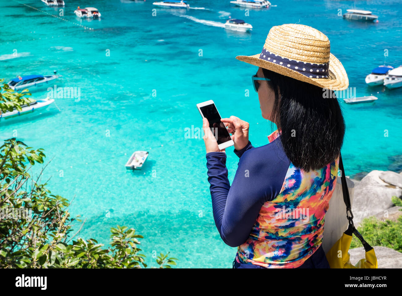 Traveller woman with colorful swimming suit use mobile take photo of  view  at top of mountain and speed boat in - Stock Image