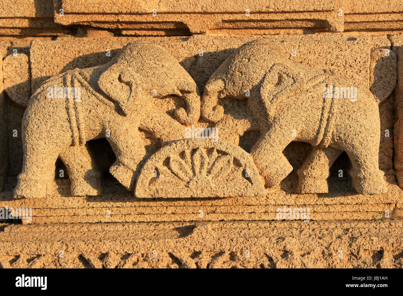 Wall carving of two elephants graciously riding over semi-circular block of lotus at Rukmini Temple on seashore - Stock Image
