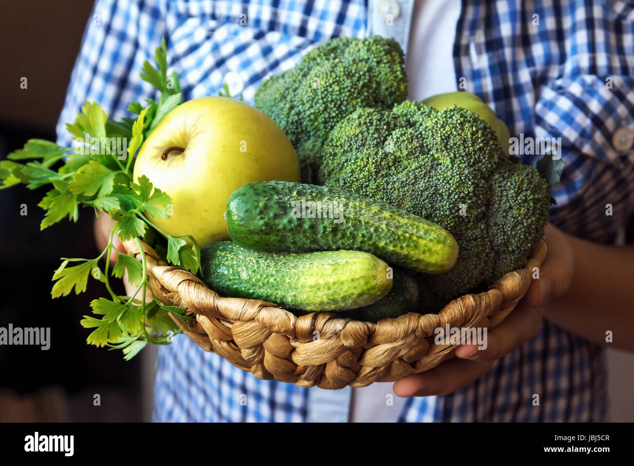 Person (hands) hold basket with organic green vegetables (broccoli, cucumbers, apple and parsley) - healthy organic Stock Photo