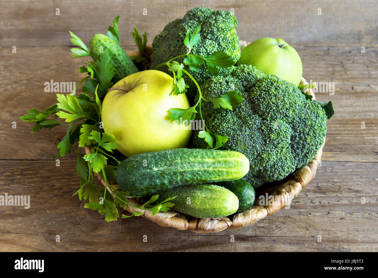 Vegetables . Assorted Organic Harvest Green Vegetables in a Basket. Fresh Vegetables over rustic wooden background. - Stock Image