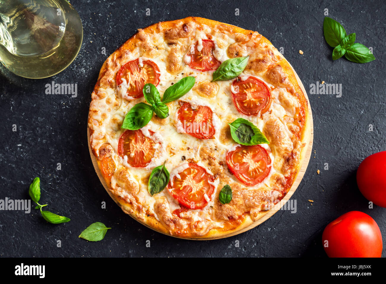 Pizza Margherita on black stone background. Homemade Pizza Margarita with Tomatoes, Basil and Mozzarella Cheese. - Stock Image