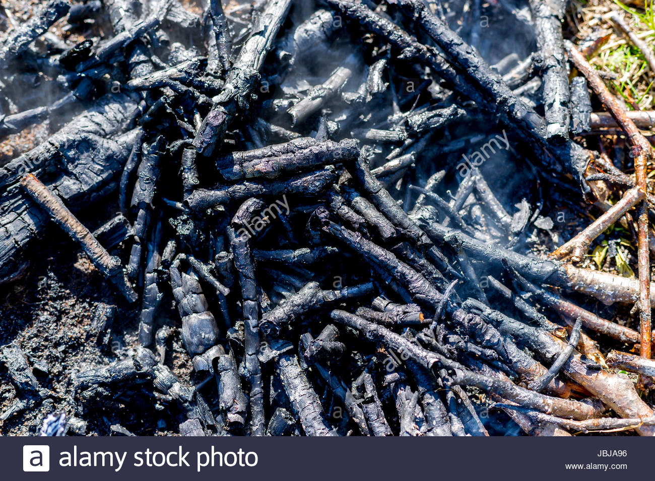 Coals from a bonfire with creeping smoke - Stock Image