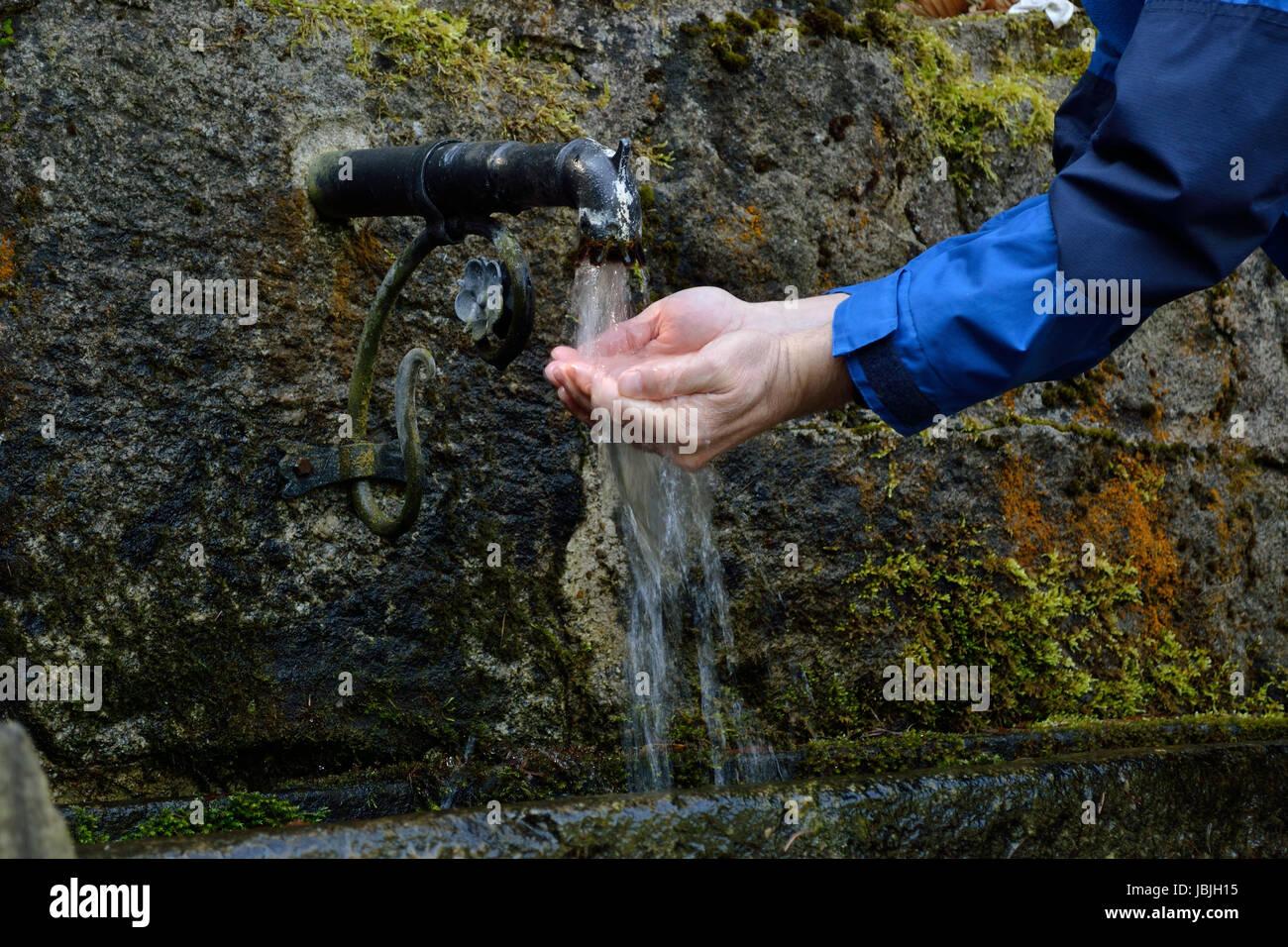 Person erfrischt sich im Freien bei einer Trinkwasserquelle Stock Photo