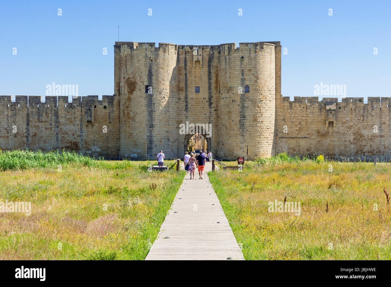 Tourists entering the old town through one of the main medieval gateways of Aigues Mortes, Nimes, Gard, Occitanie, - Stock Image