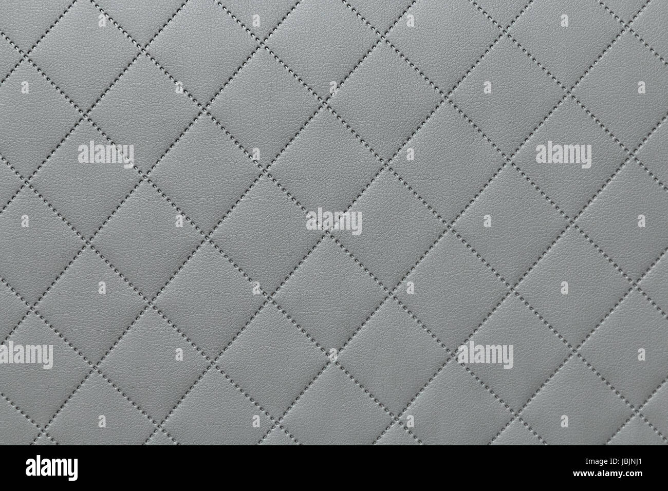 detail of sewn leather, gray leather upholstery background pattern - Stock Image