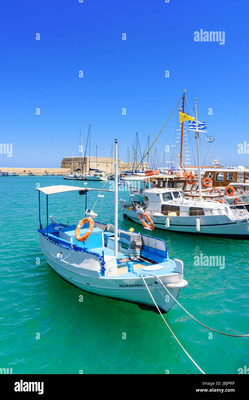 Fishing boats moored in the inner harbour with the Koules Fortress in the background, Heraklion, Crete, Greece Stock Photo