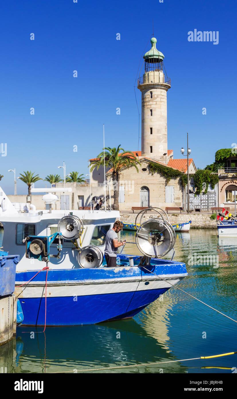 Moored fishing boats and the landmark stone lighthouse along the Chenal Maritime, Le Grau-du-Roi, Gard, France - Stock Image