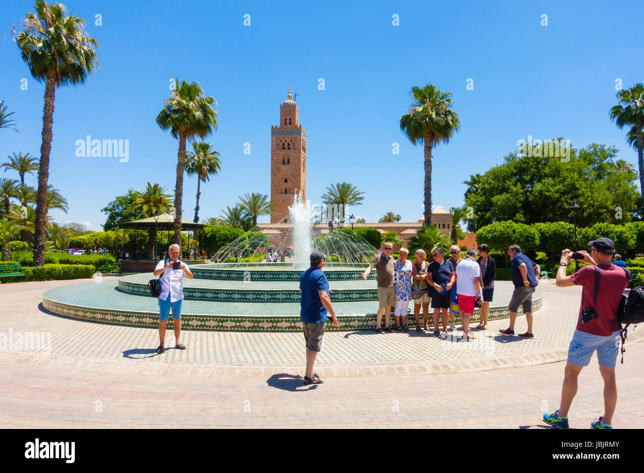 Marrakech, Morocco -  May 12, 2017: A group of tourists taking photos of each other in front of the fountain in - Stock Image