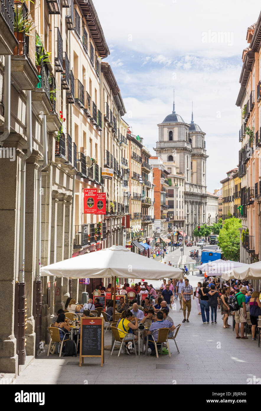 Busy tapas cafes and restaurants along Calle de Toldeo looking towards the imposing Basilica de San Isidro, Madrid, - Stock Image