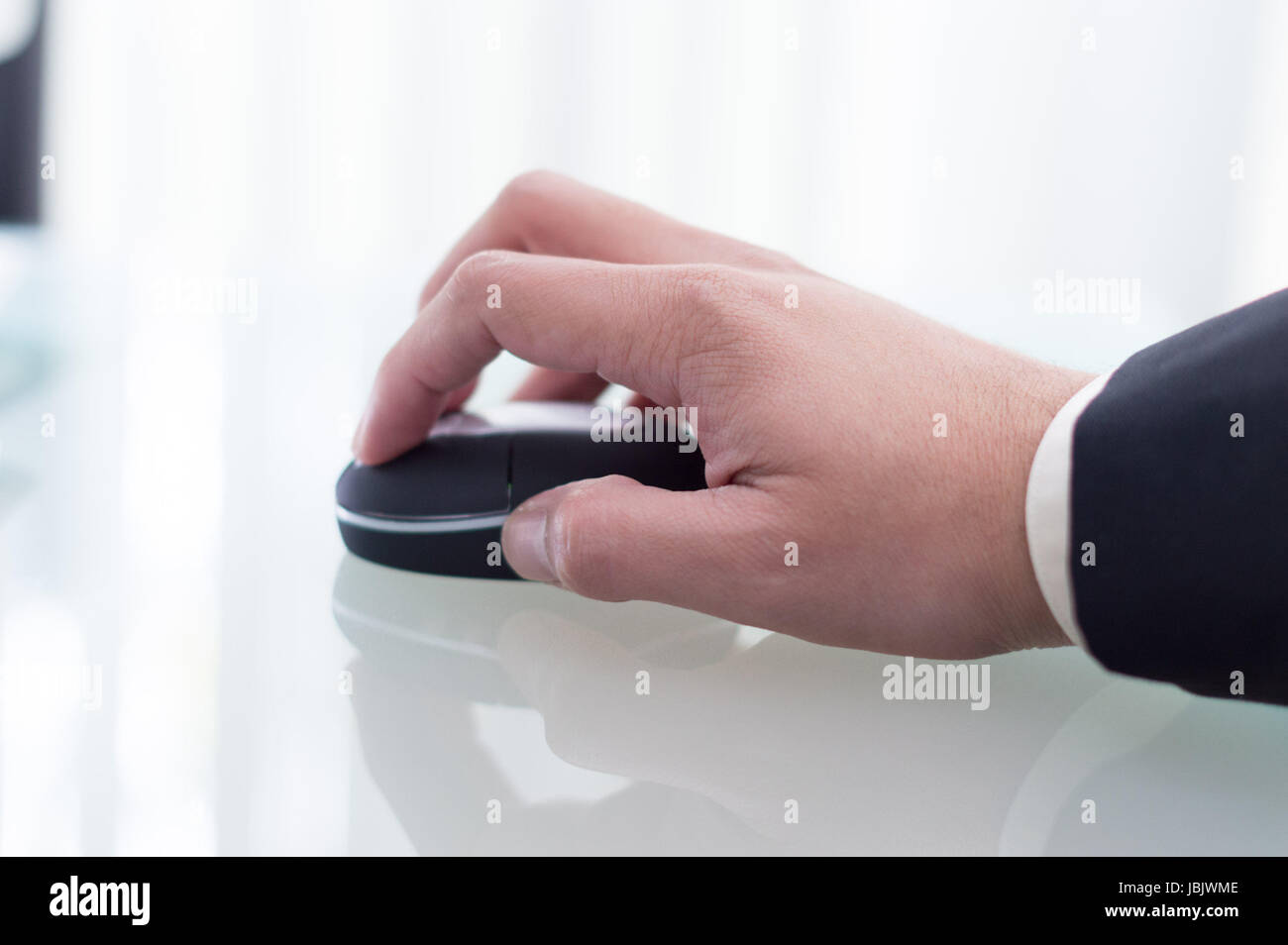 Bussiness man in a black suit using a black wireless mouse at his office - Stock Image