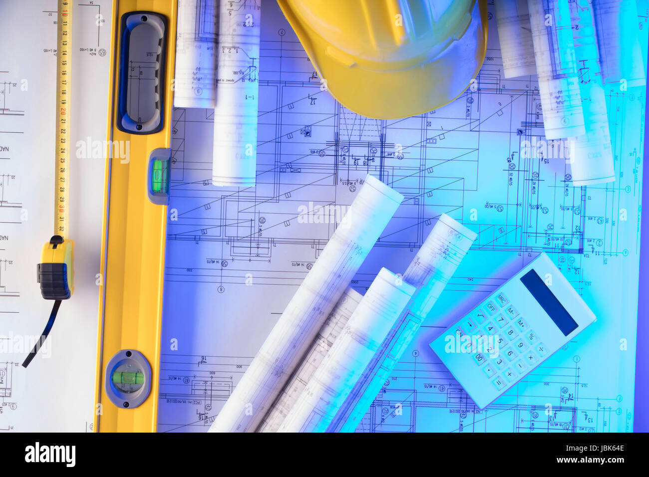 Rolls with building projects, equipment of architect: crash helmet and spirit level on wooden table. - Stock Image