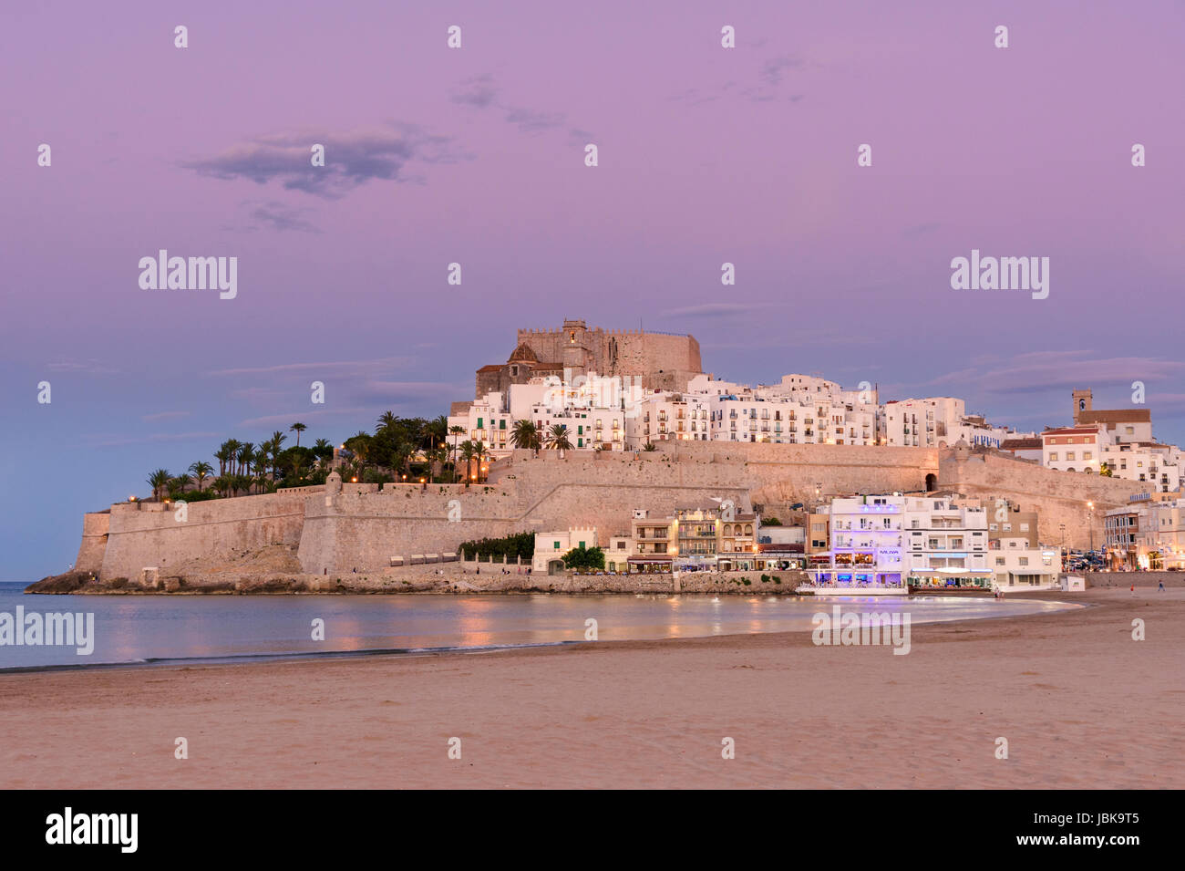 Sunset over Papa Luna Castle and old town overlooking the beach of Playa Norte, Peniscola, Castellon, Spain - Stock Image