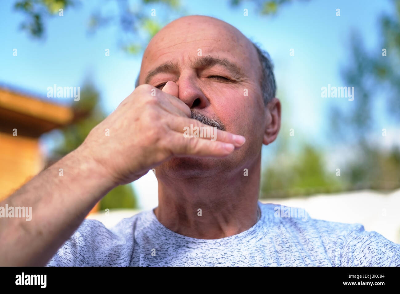 Handsome mature man with mustache breathing yoga pranayama on summer sunny day outside. - Stock Image