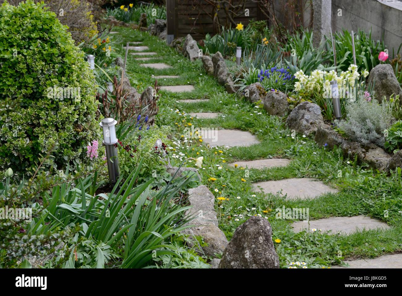Steinplatten Bilden Weg Durch Einen Blumigen Garten   Stock Image