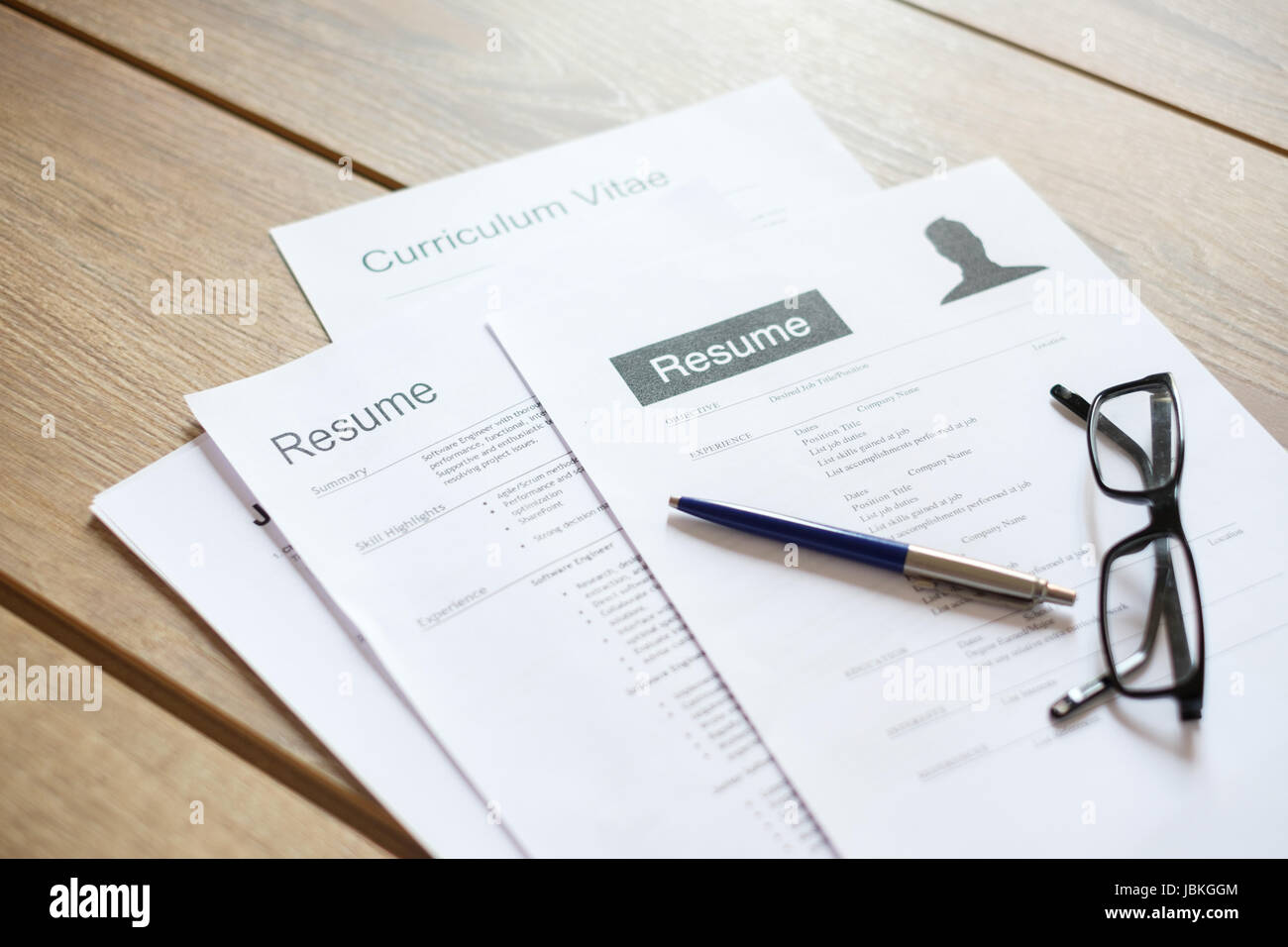 Resume applications on wooden desk ready to be reviewed Stock Photo
