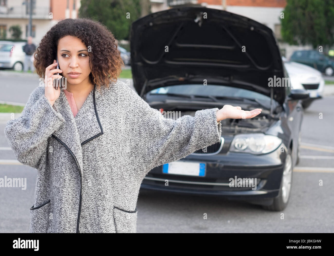Desperate woman calling for emergency help after vehicle breakdown - Stock Image