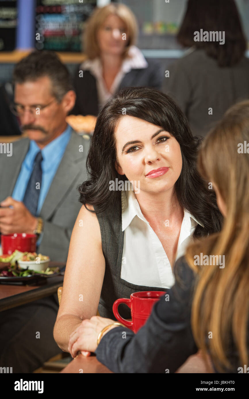 Grinning woman consoled by friend in cafeteria - Stock Image