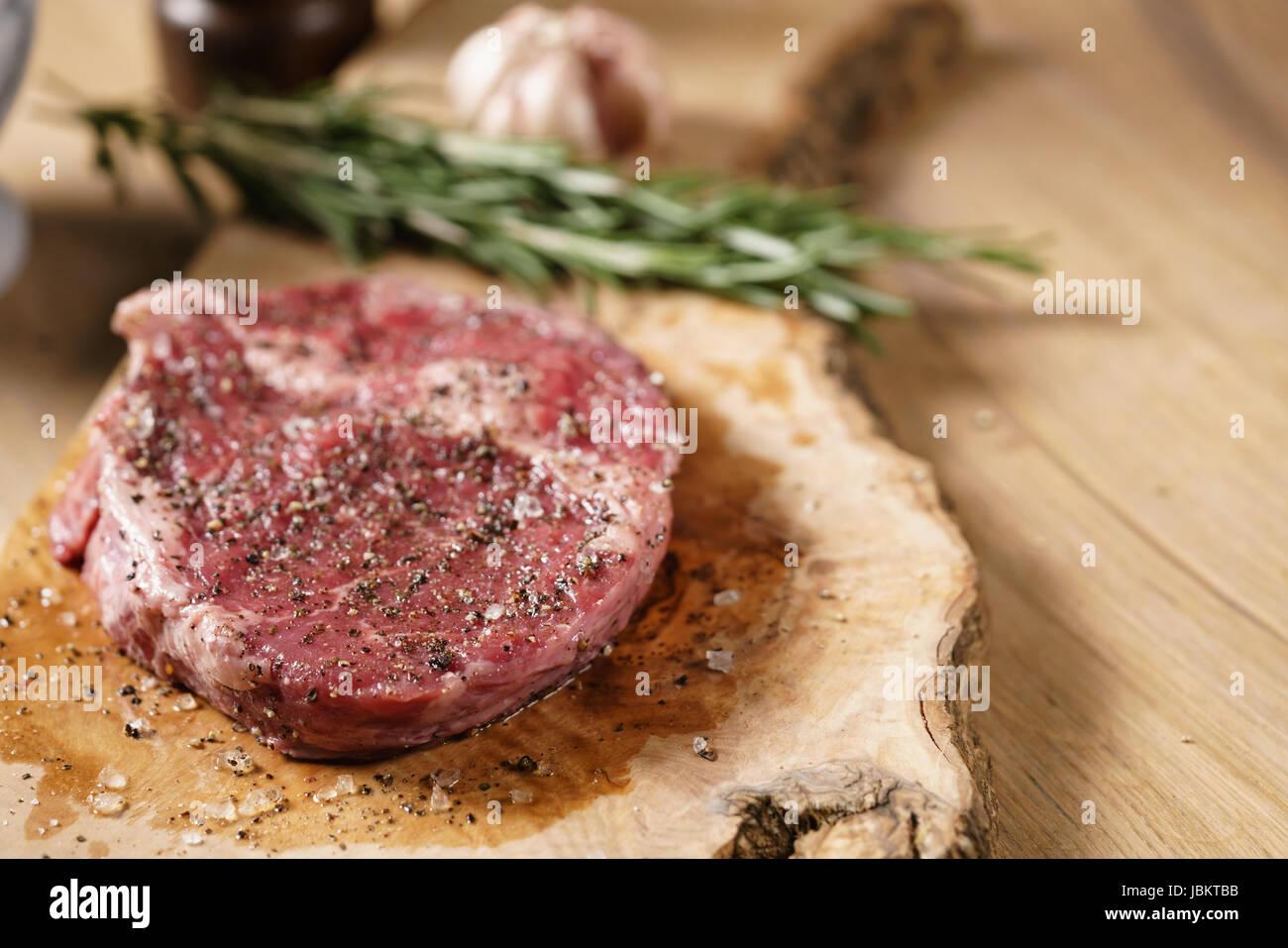 raw rib eye steak on board closeup - Stock Image