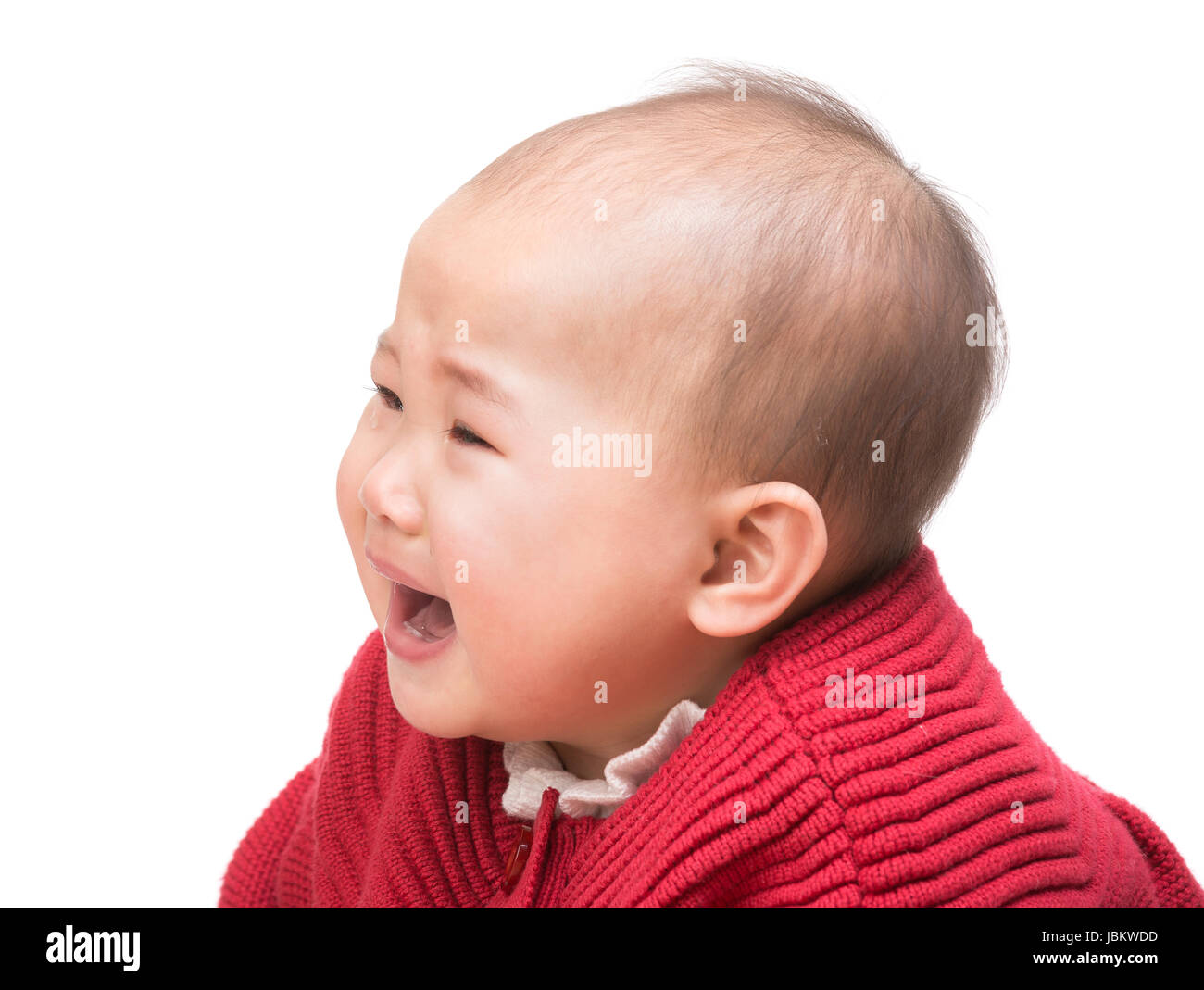 Crying baby girl and looking aside - Stock Image