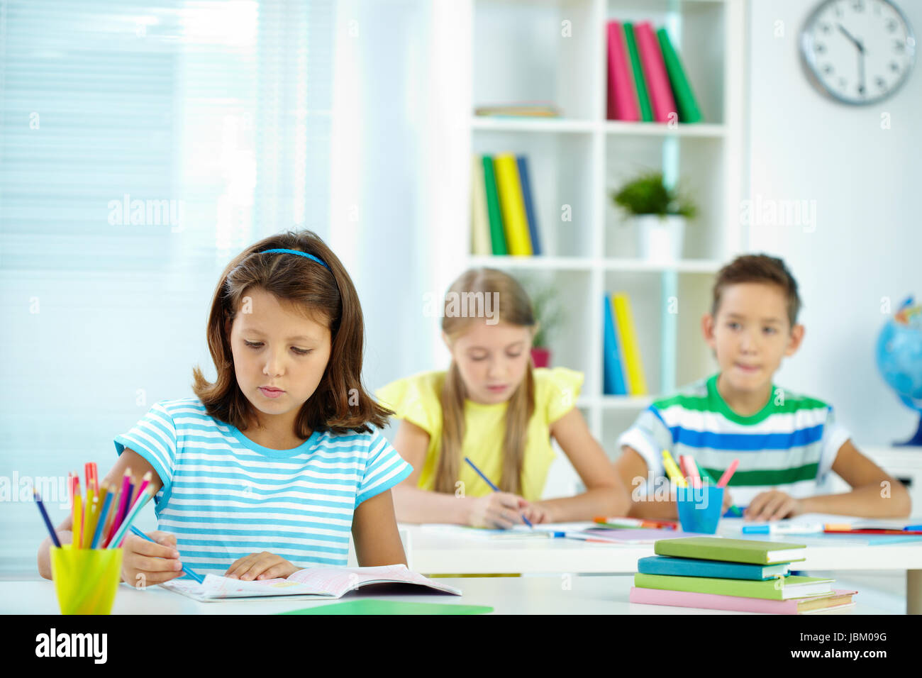 Serious girl drawing at workplace with schoolmates on background - Stock Image