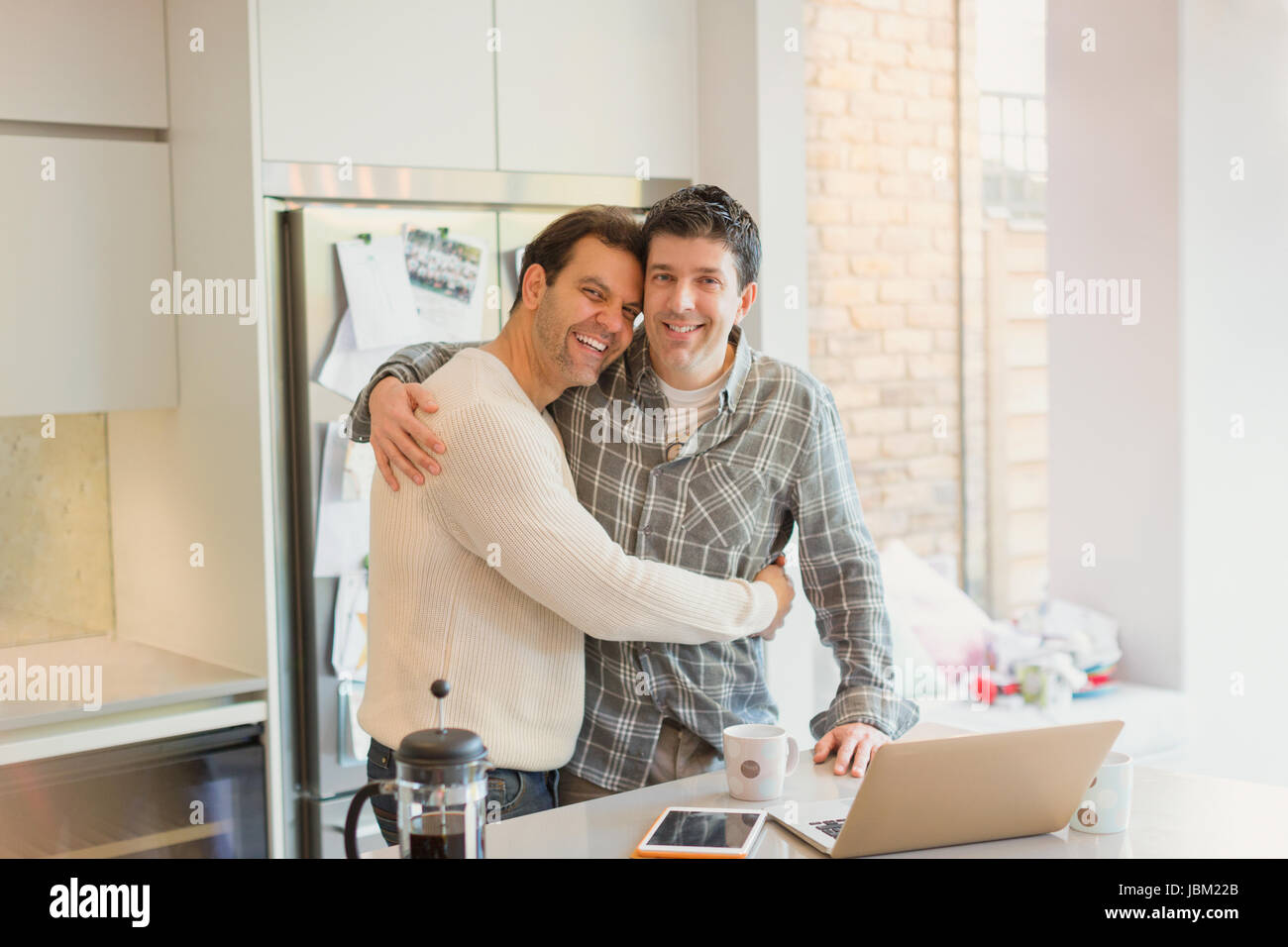 1f391f2441 Portrait affectionate male gay couple hugging at laptop in kitchen - Stock  Image