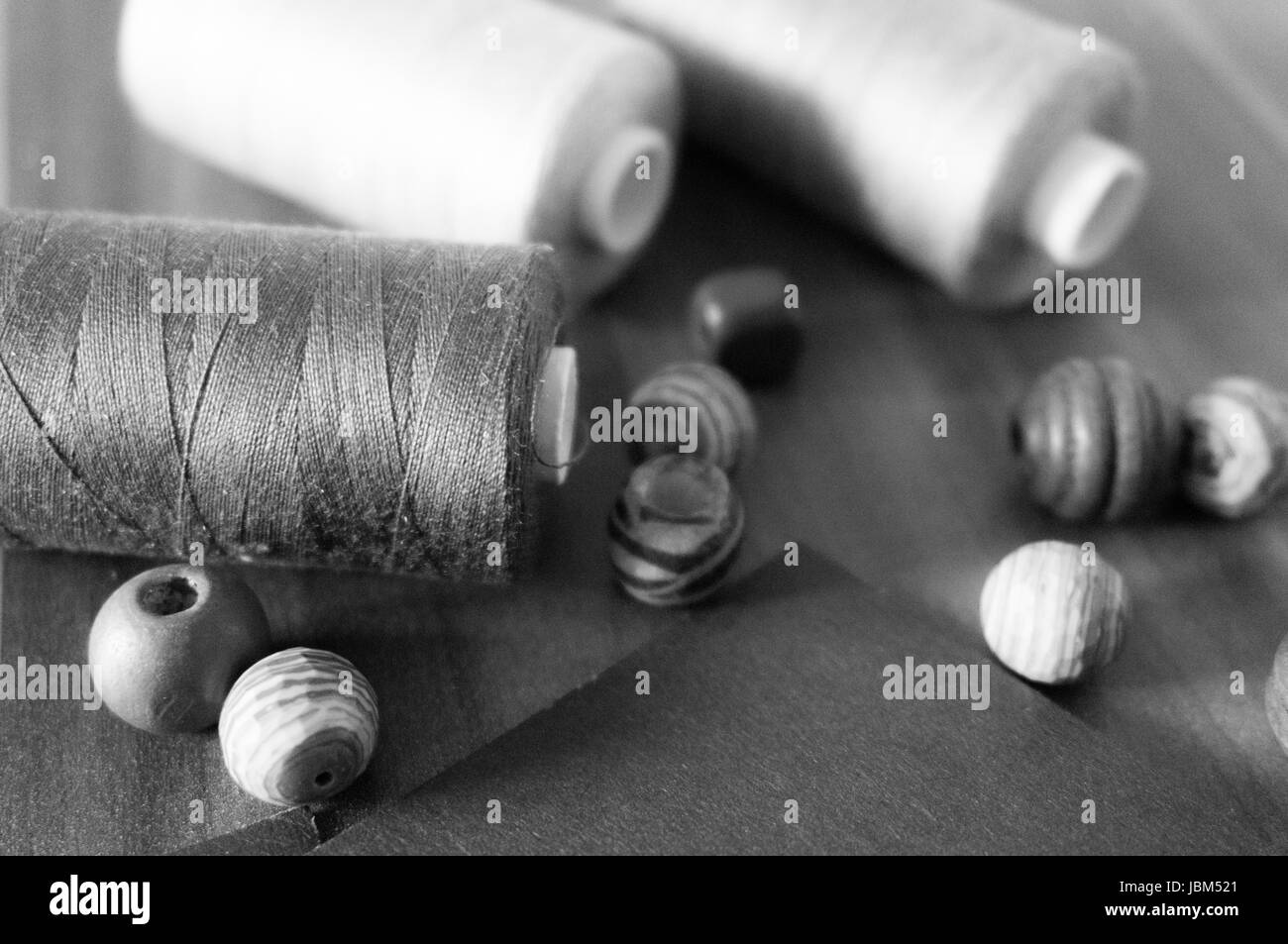 Thread, beads and paper close-up (desaturated) - Stock Image