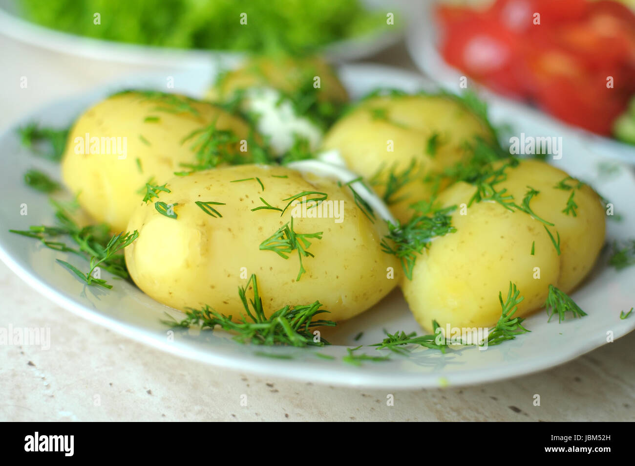 Fresh organic vegetables and boiled new potatoes on the plates on the wooden table. Close up, selective focus. - Stock Image
