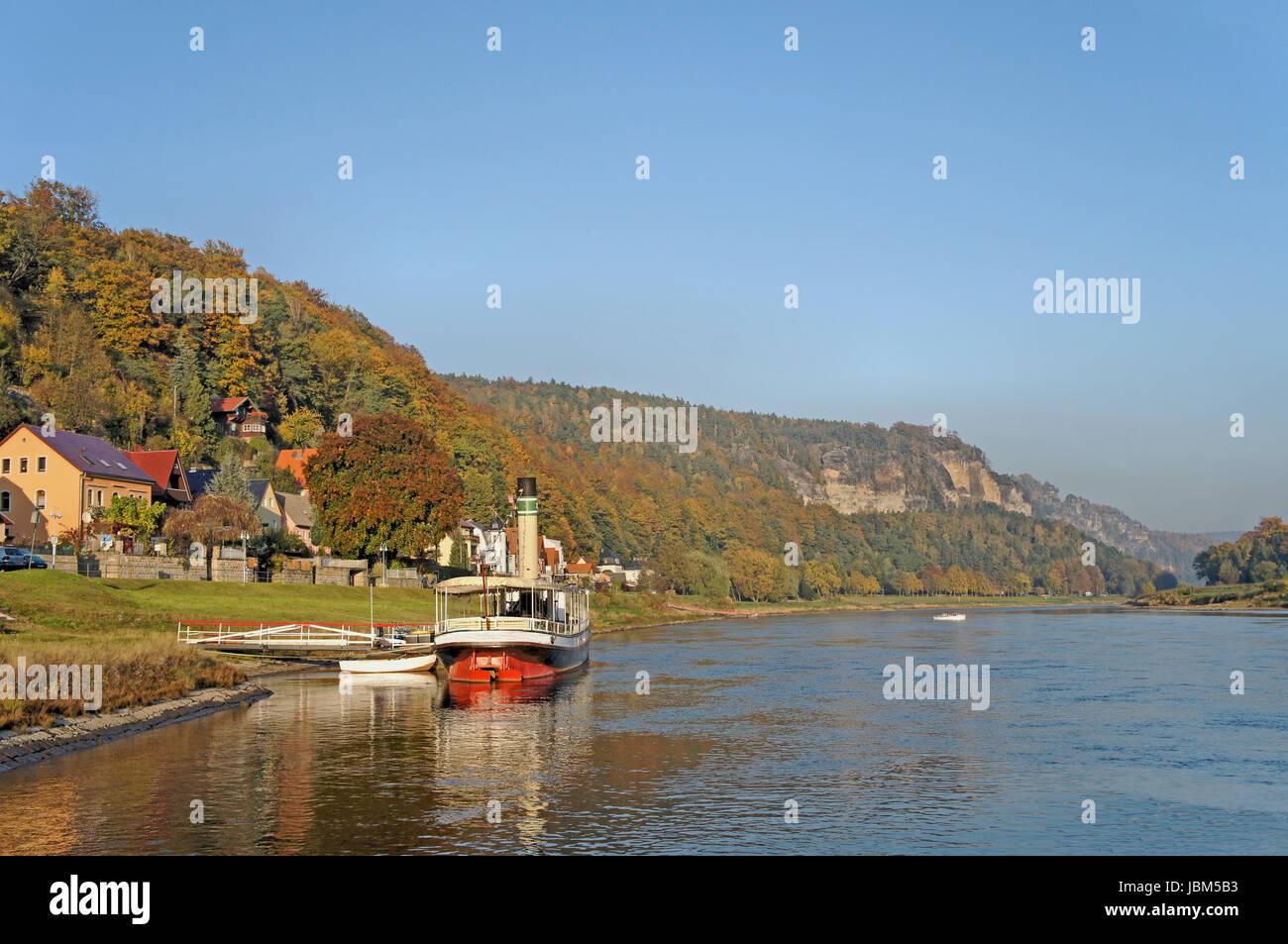 Die Elbe im deutschen Teil des Elbsandsteingebirges; steile Felsen und bunte Laubwälder; am Ufer ein kleiner Dampfer Stock Photo