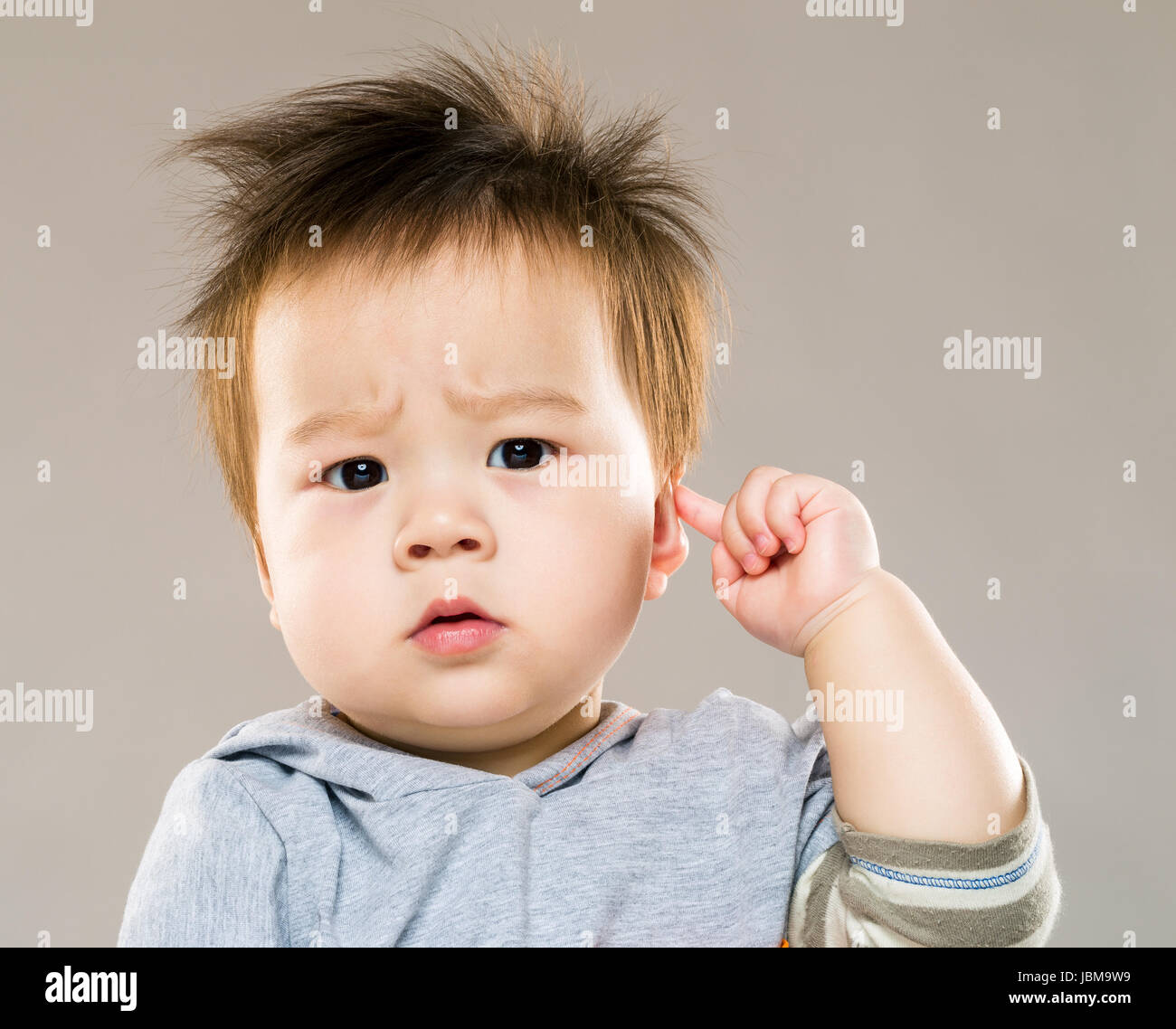 Baby boy touch his ear - Stock Image