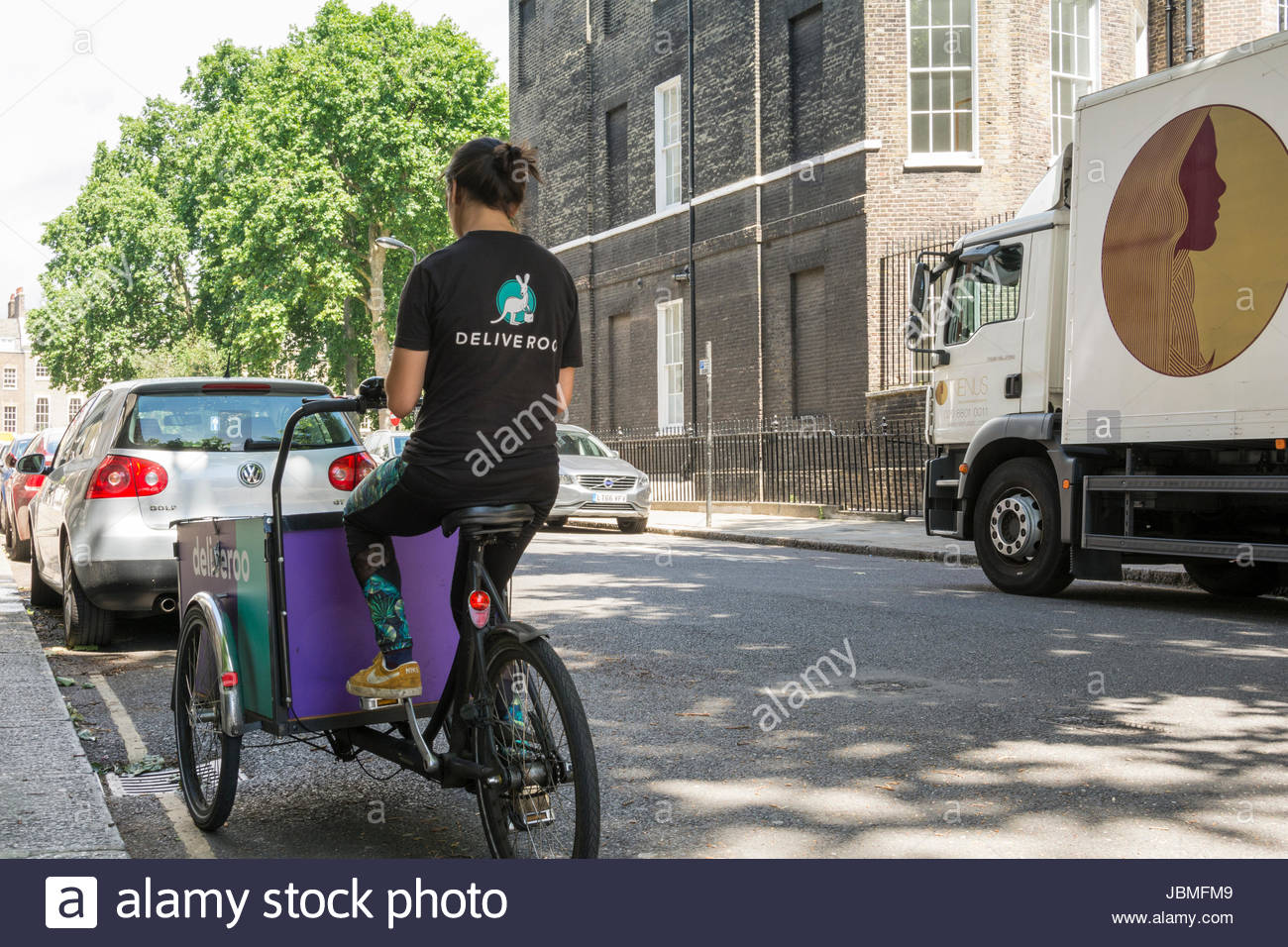 A female Deliveroo rider waits for her next job in London, UK - Stock Image