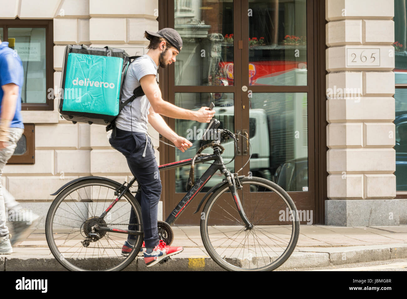A Deliveroo cyclist picking-up his next job on his mobile phone in central London, UK - Stock Image