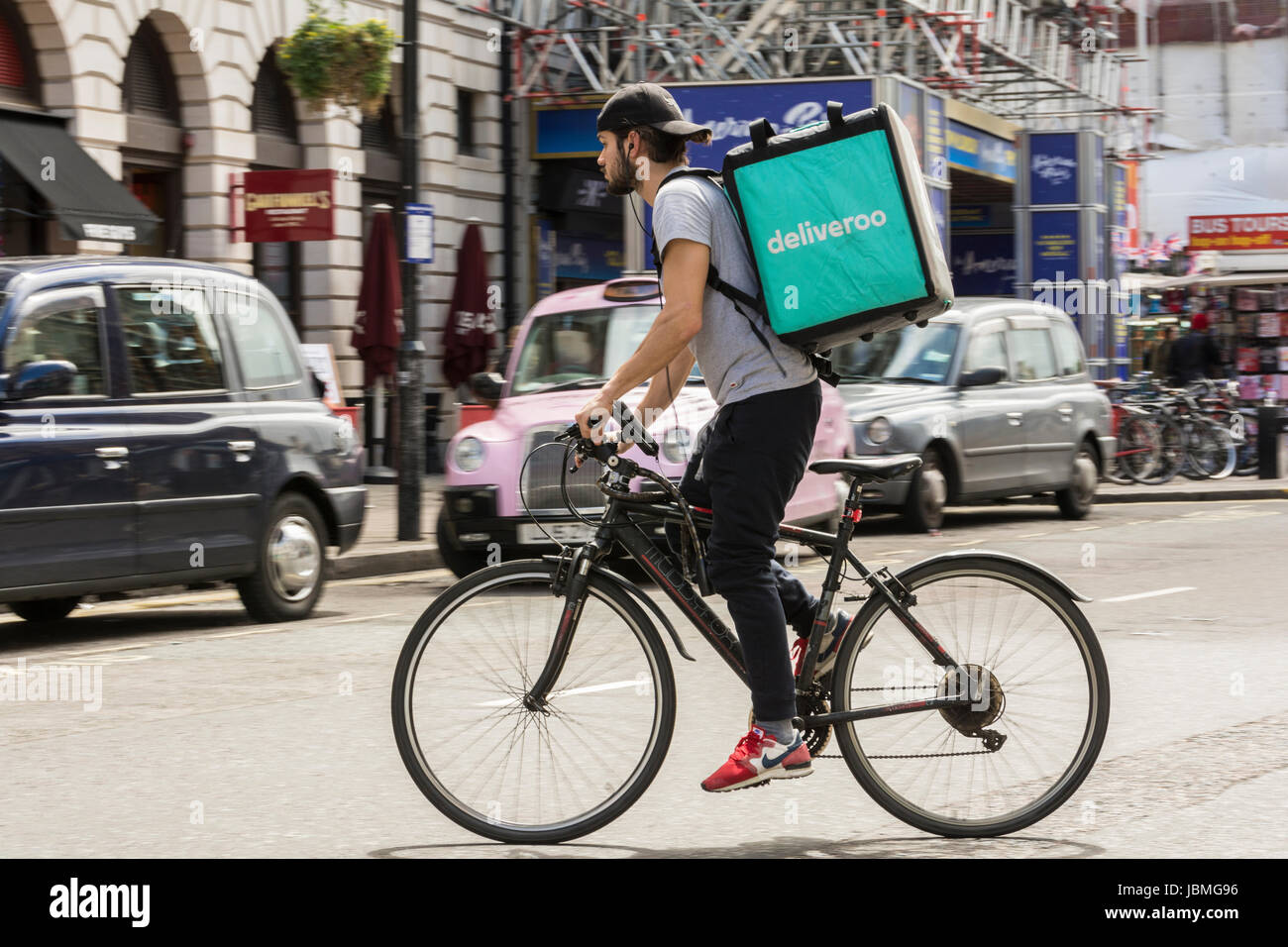 A Deliveroo cyclist on his bike in central London, UK - Stock Image